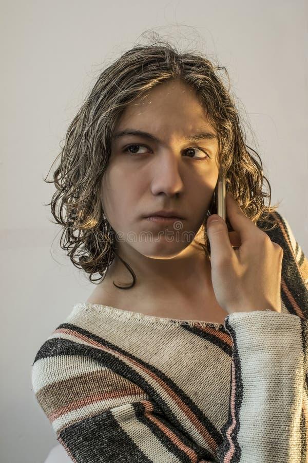Το νέο αγόρι έντυσε στο πουλόβερ με το κινητό τηλέφωνο στοκ εικόνες