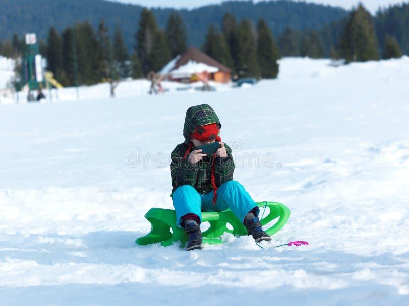 Το νέο αγόρι έχει τη διασκέδαση στο χειμώνα vacatioin και παίζει τα παιχνίδια στο τηλέφωνο στοκ εικόνα με δικαίωμα ελεύθερης χρήσης