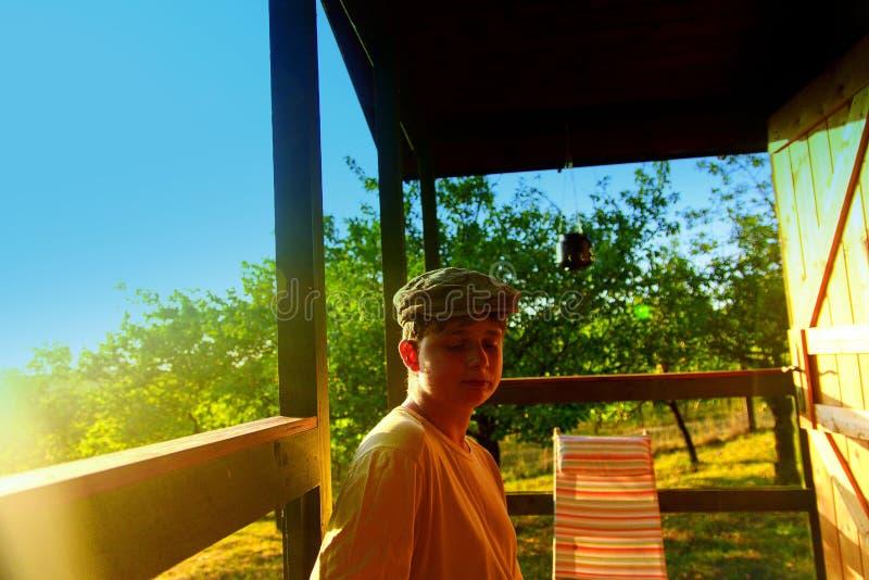 Το νέο αγόρι κάθεται σε μια βεράντα Ονειροπόλος και ρομαντική εικόνα Καλοκαίρι και ευτυχής έννοια παιδικής ηλικίας στοκ εικόνες