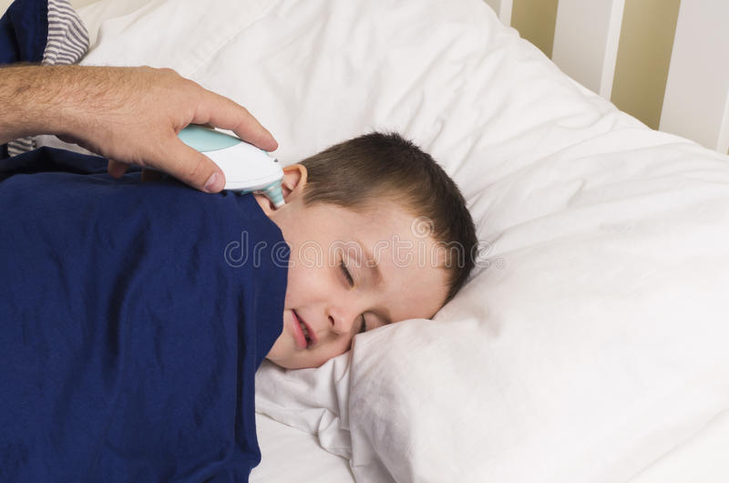 Το νέο αγόρι παίρνει τη θερμοκρασία του με ένα digitial θερμόμετρο στοκ φωτογραφίες με δικαίωμα ελεύθερης χρήσης