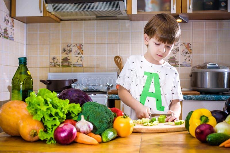 Το νέο αγόρι στο μαγείρεμα που στέκεται στην κουζίνα κοντά στον πίνακα με στοκ εικόνες