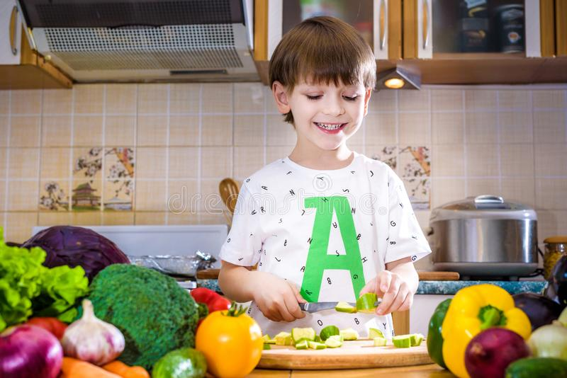 Το νέο αγόρι στο μαγείρεμα που στέκεται στην κουζίνα κοντά στον πίνακα με στοκ φωτογραφία