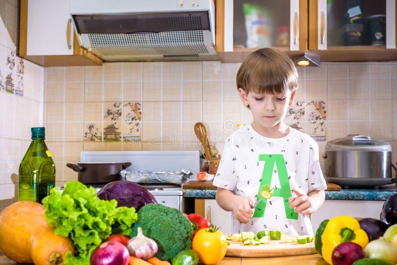 Το νέο αγόρι στο μαγείρεμα που στέκεται στην κουζίνα κοντά στον πίνακα με στοκ εικόνα με δικαίωμα ελεύθερης χρήσης