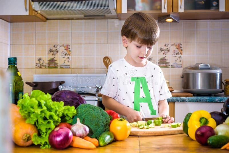 Το νέο αγόρι στο μαγείρεμα που στέκεται στην κουζίνα κοντά στον πίνακα με στοκ εικόνα