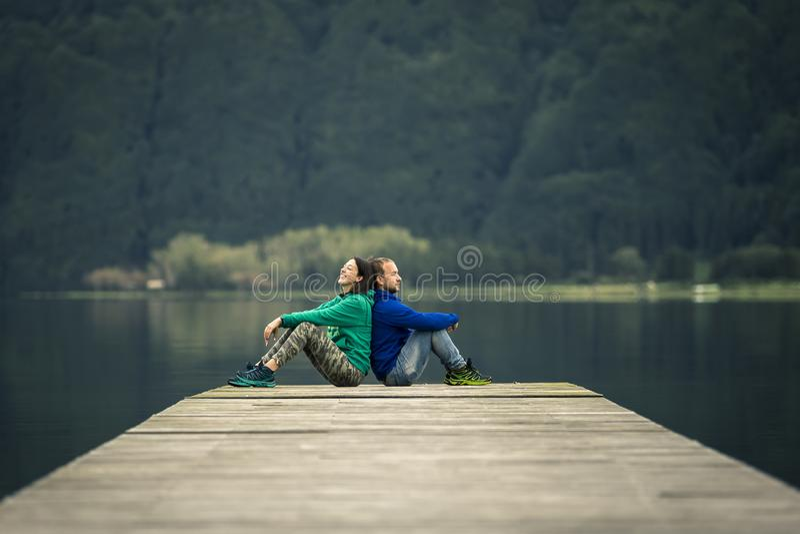 Το νέο ακριβώς παντρεμένο ζευγάρι κάθεται στην αποβάθρα από την ηφαιστειακή λίμνη στοκ εικόνα με δικαίωμα ελεύθερης χρήσης