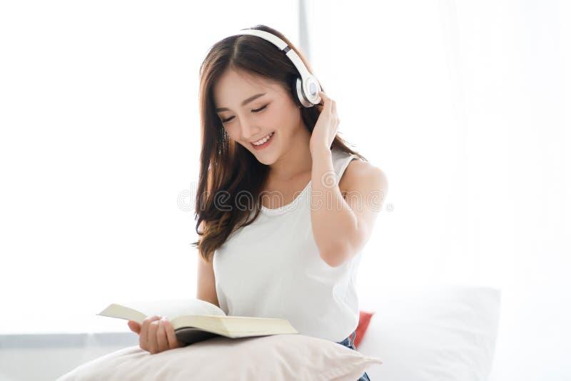 Το νέο αρκετά ασιατικό βιβλίο ανάγνωσης γυναικών και και η μουσική ακούσματος στα σύγχρονα ακουστικά σύνδεσαν με το smartphone στ στοκ εικόνες