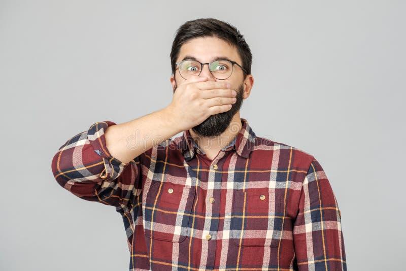 Το νέο αρσενικό πρότυπο καλύπτει το στόμα με τα χέρια που απομονώνονται πέρα από γκρίζο στοκ εικόνες