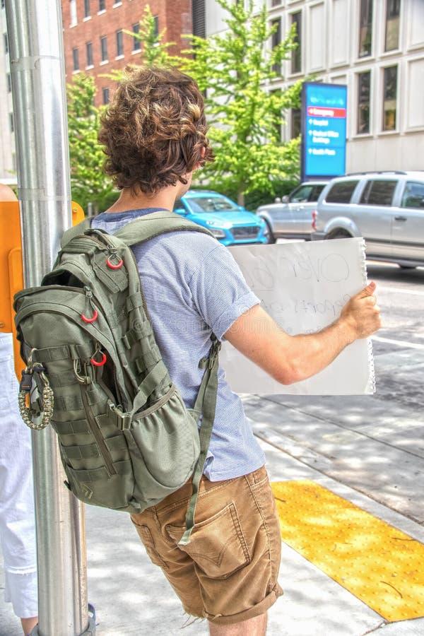 Το νέο αρσενικό protestor με τα χακί σορτς και το σακίδιο πλάτης κλίνει στον ελαφρύ πόλο και κρατά ψηλά το σημάδι εκτός από την ο στοκ εικόνα με δικαίωμα ελεύθερης χρήσης