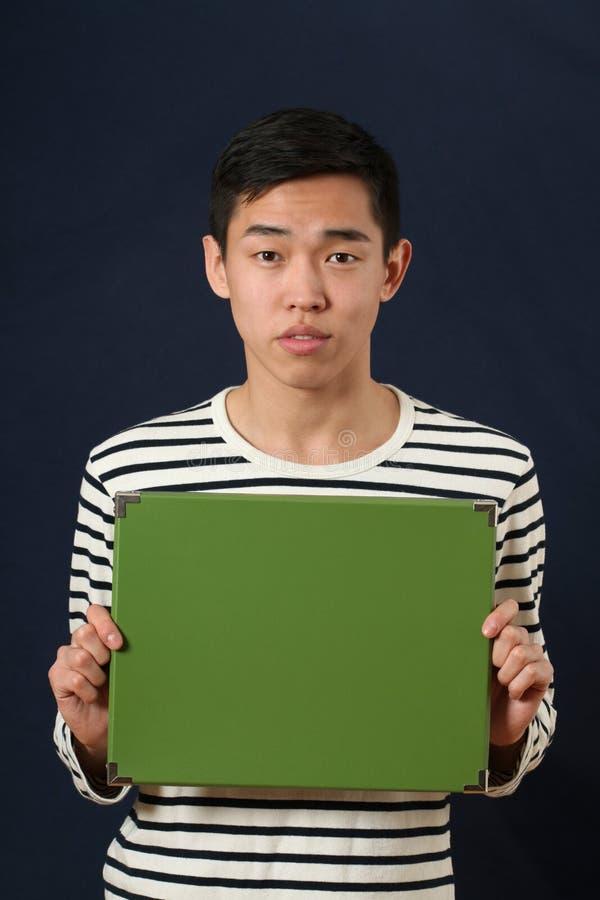 Το νέο ασιατικό άτομο που παρουσιάζει στο πράσινο αντίγραφο διαστημικό κιβώτιο και που εξετάζει ήρθε στοκ φωτογραφίες