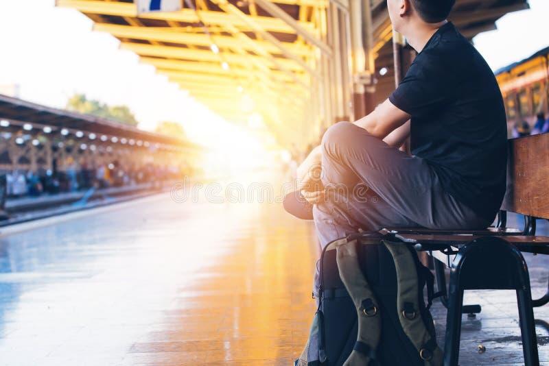 Το νέο ασιατικό αρσενικό ταξίδι backpacker κάθεται και περιμένει ένα τραίνο στην πλατφόρμα σιδηροδρόμων στη Μπανγκόκ, Ταϊλάνδη στοκ φωτογραφίες με δικαίωμα ελεύθερης χρήσης