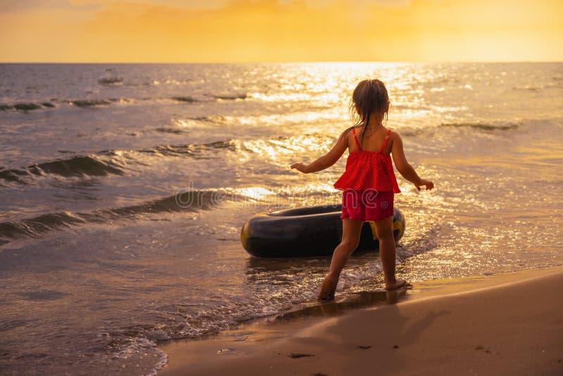 Το νέο ασιατικό αστείο παιχνίδι κοριτσιών κολυμπά το δαχτυλίδι στην παραλία στο ηλιοβασίλεμα στοκ εικόνα με δικαίωμα ελεύθερης χρήσης