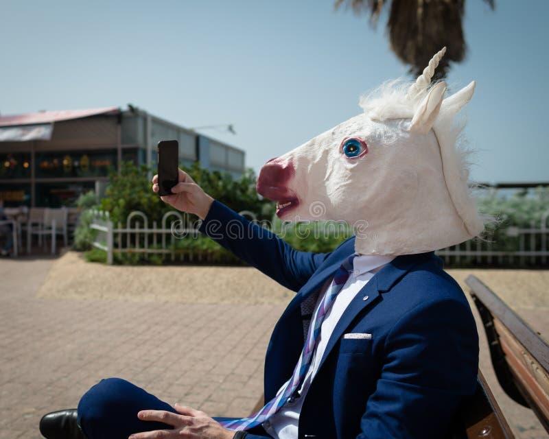 Το νέο ασυνήθιστο άτομο στην κωμική μάσκα και το κομψό κοστούμι κάνει μια φωτογραφία τηλεφωνικώς στοκ φωτογραφία με δικαίωμα ελεύθερης χρήσης
