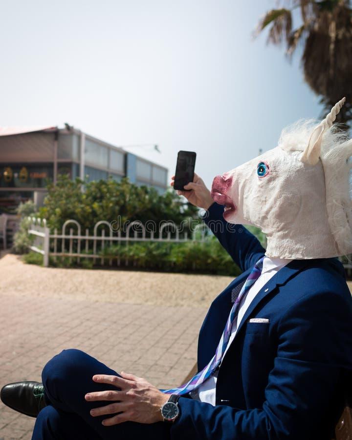 Το νέο ασυνήθιστο άτομο στη μάσκα κεφαλιών αλόγων και το κομψό κοστούμι κάνει μια φωτογραφία τηλεφωνικώς στοκ εικόνες