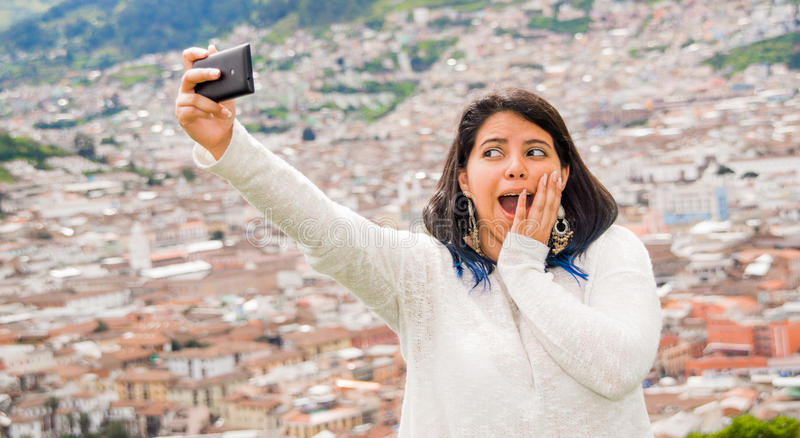 Το νέο λατινικό κορίτσι παίρνει ένα selfie με το τηλέφωνό του στο καλοκαίρι, πίσω από μια αστική πόλη, φαίνεται έκπληκτη της όμορ στοκ φωτογραφία με δικαίωμα ελεύθερης χρήσης
