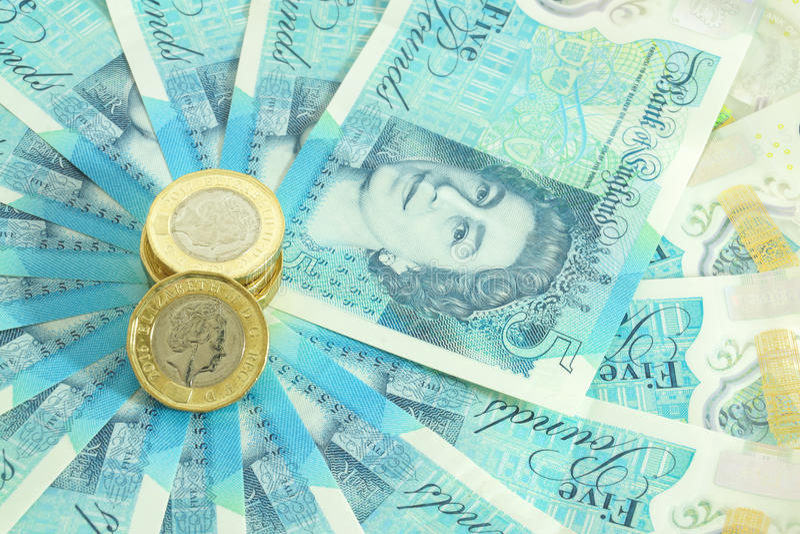 Το νέο βρετανικό πολυμερές σώμα σημείωση πέντε λιβρών και τα νέα 12 πλαισίωσε το νόμισμα £1 στοκ εικόνες