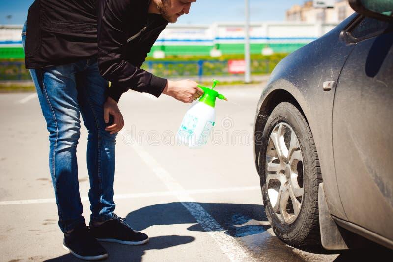 το νέο γενειοφόρο άτομο πλένει τα πλαίσια ροδών αυτοκινήτων του ` s, που ψεκάζουν το νερό από τον ψεκασμό στοκ εικόνα με δικαίωμα ελεύθερης χρήσης