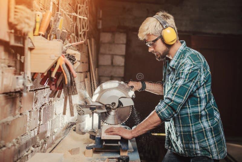 Το νέο γενειοφόρο άτομο hipster με τους προστάτες αυτιών από τα πριόνια οικοδόμων ξυλουργών επαγγέλματος με μια εγκύκλιο είδε ένα στοκ φωτογραφία