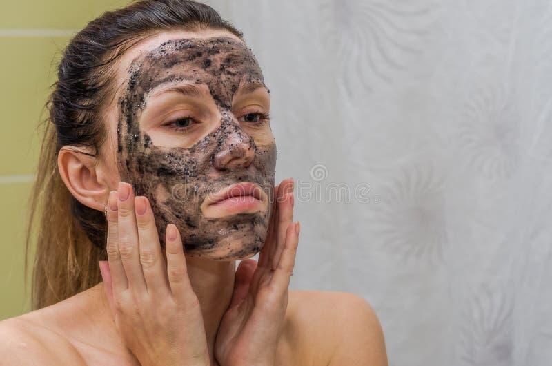 Το νέο γοητευτικό κορίτσι κάνει μια μαύρη μάσκα ξυλάνθρακα στο πρόσωπό της στοκ φωτογραφία