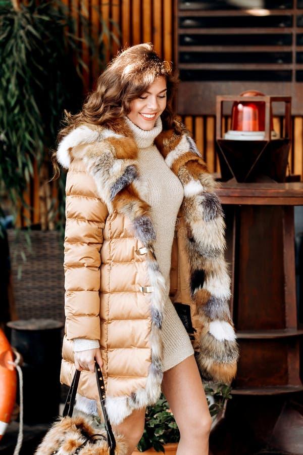 Το νέο γοητευτικό κορίτσι που ντύνεται στο μπεζ πλέκει το φόρεμα και ένα ανοικτό καφέ κάτω σακάκι με τη γούνα θέτει στην οδό στοκ φωτογραφίες