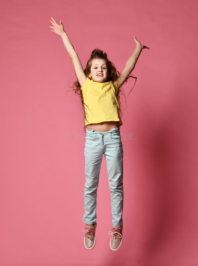 Το νέο γυναικείο ή εφήβων κορίτσι στα τζιν και την κίτρινη μπλούζα με τα χέρια της προσπαθεί επάνω να πηδήσει τόσο υψηλό όσο μπορ στοκ φωτογραφία με δικαίωμα ελεύθερης χρήσης
