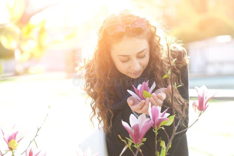Το νέο δέντρο λουλουδιών magnolia γυναικών ανθίζοντας πλησίον σταθμεύει την άνοιξη την ηλιόλουστη ημέρα Όμορφο ευτυχές κορίτσι πο στοκ εικόνες