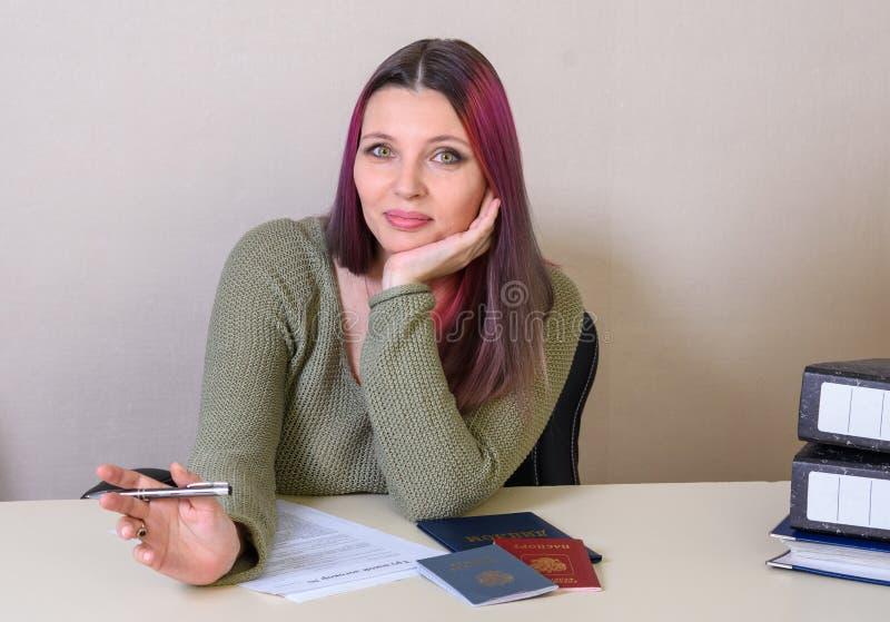 Το νέο δημιουργικό κορίτσι συμπληρώνει μια σύμβαση απασχόλησης και ένα αρχείο απασχόλησης, το διαβατήριο και το δίπλωμα στον πίνα στοκ φωτογραφία με δικαίωμα ελεύθερης χρήσης