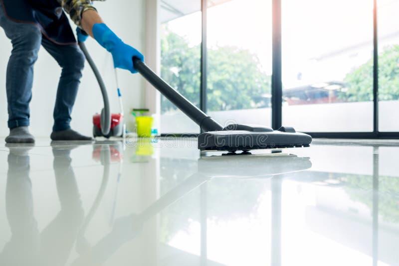 Το νέο ελκυστικό άτομο καθαρίζει τον κενό εμπορικό καθαρίζοντας εξοπλισμό στο πάτωμα που βοηθά στο σπίτι τη σύζυγο στοκ φωτογραφία