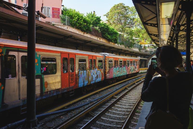 Το νέο ελκυστικό κορίτσι παίρνει τις εικόνες ενός χρωματισμένου φωτεινού τραίνου στον υπόγειο στο smartphone της στοκ εικόνα με δικαίωμα ελεύθερης χρήσης