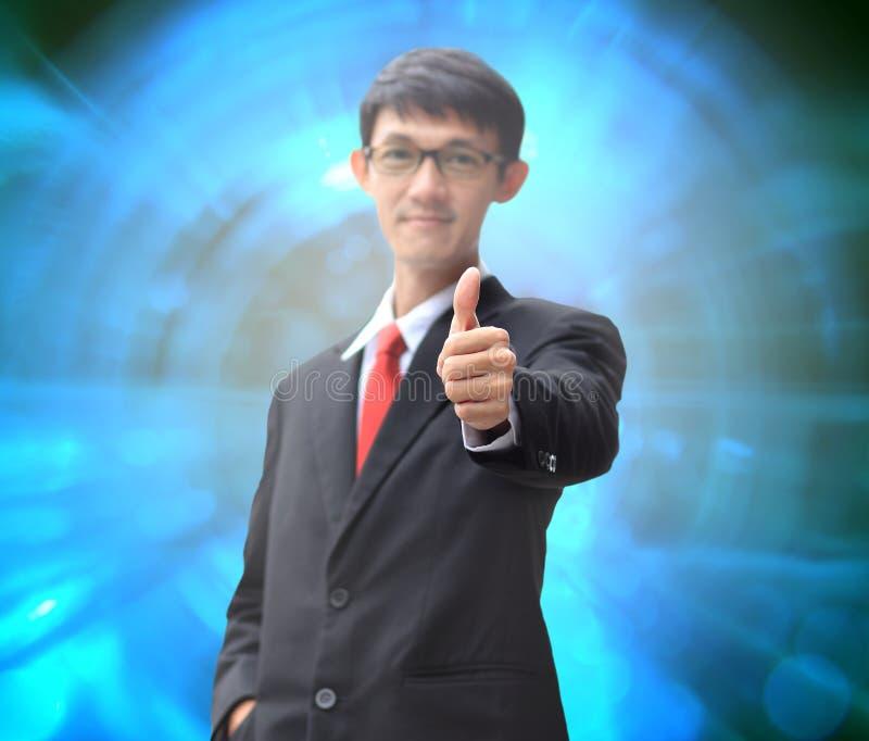Το νέο επιχειρησιακό άτομο σε ένα κοστούμι που δείχνει με το δάχτυλό του φυλλομετρεί επάνω στοκ εικόνα