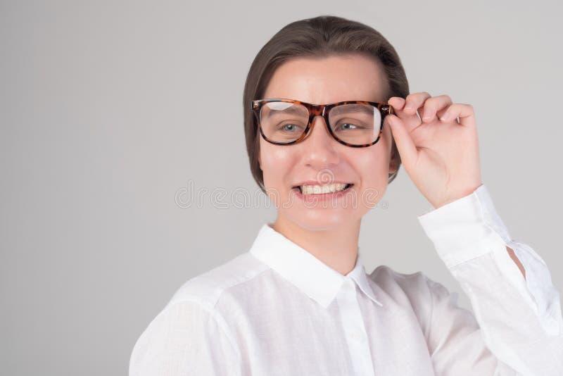 Το νέο ευτυχές επιχειρησιακό κορίτσι αγγίζει τα γυαλιά της στοκ εικόνες