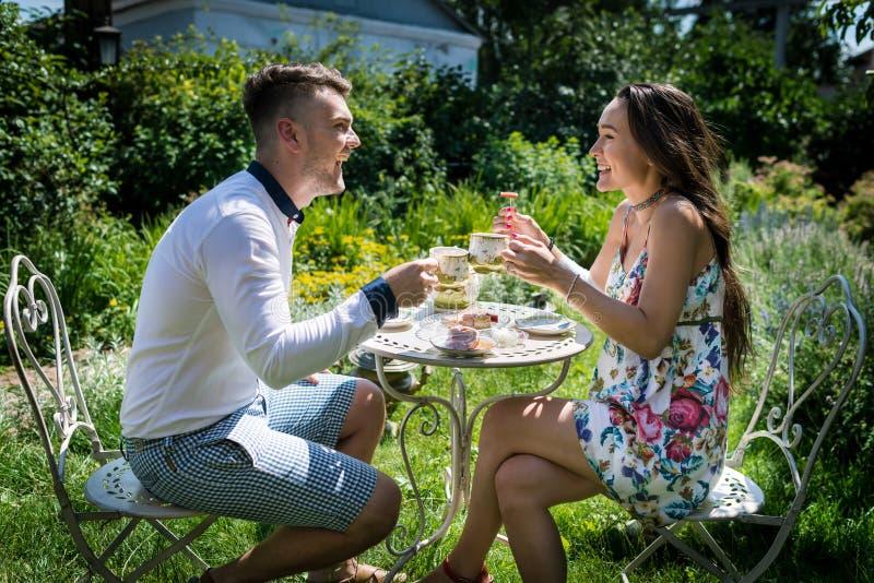 Το νέο ευτυχές ζεύγος κάθεται στον πίνακα και κρατά τα φλυτζάνια με το τσάι στον κήπο στοκ φωτογραφία με δικαίωμα ελεύθερης χρήσης