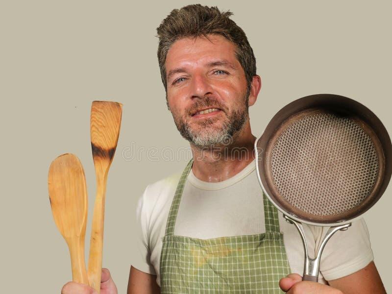 Το νέο ευτυχές και ελκυστικό άτομο εγχώριων μαγείρων στην ποδιά που χαμογελά το εύθυμα και γοητευτικά τηγάνι και το κουτάλι κουζι στοκ εικόνα