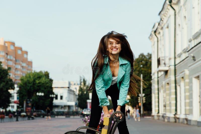 Το νέο ευτυχές κορίτσι, που έχει τη διασκέδαση, πηδά και έχει τη διασκέδαση στην οδό lifestyle στοκ φωτογραφία