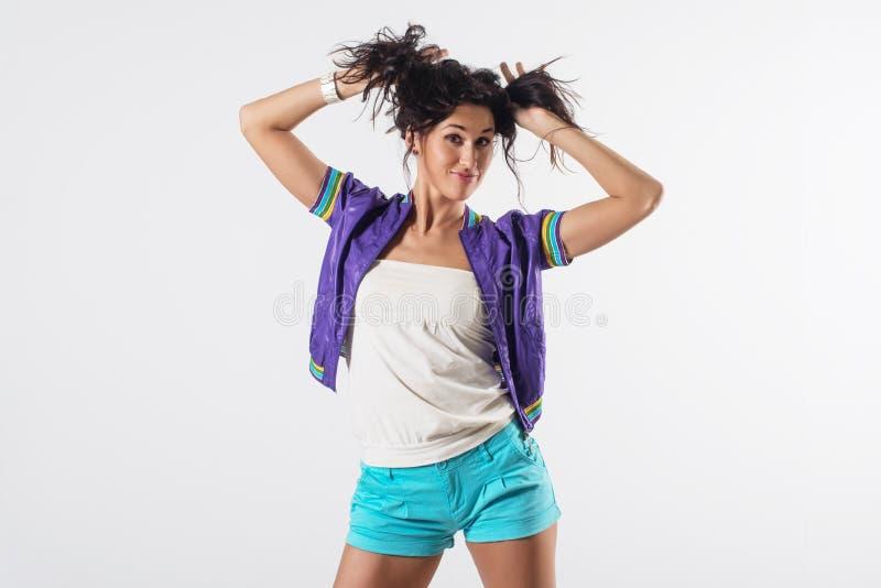 Το νέο ευτυχές κορίτσι που κρατά την τρίχα της, μίμηση παρακολουθεί hairstyle, φορώντας την καθιερώνουσα τη μόδα εξάρτηση στοκ φωτογραφία με δικαίωμα ελεύθερης χρήσης