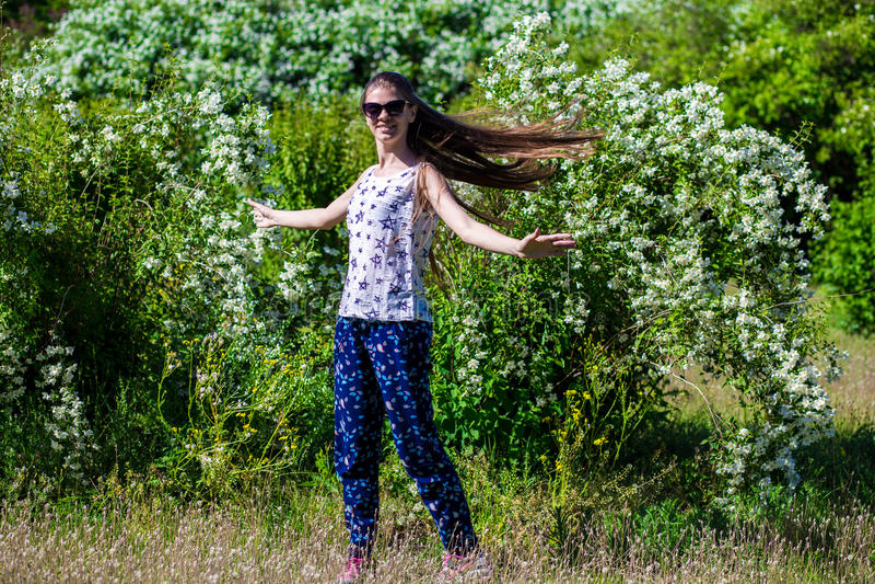 Το νέο ευτυχές κορίτσι χορεύει στο πάρκο στοκ εικόνα