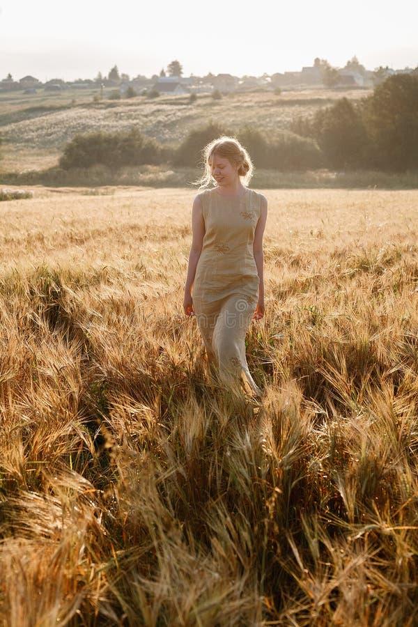 Το νέο ευτυχές όμορφο κορίτσι στο κίτρινο φόρεμα περπατά στον τομέα των αυτιών στις ακτίνες του ήλιου αύξησης άλσος και χωριό στο στοκ φωτογραφία με δικαίωμα ελεύθερης χρήσης