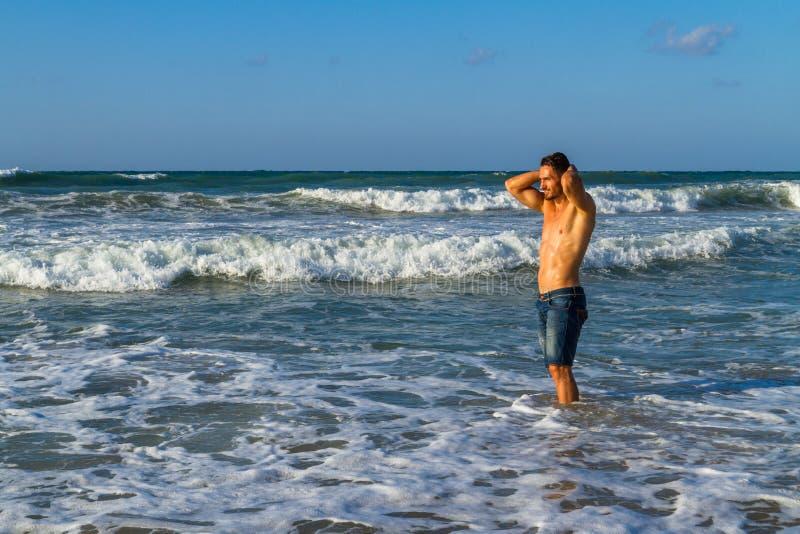 Το νέο ελκυστικό άτομο απολαμβάνει στον ωκεανό στοκ φωτογραφία