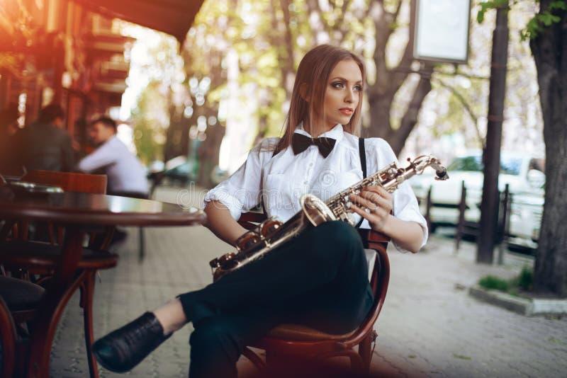 Το νέο ελκυστικό κορίτσι στο άσπρο πουκάμισο με μια συνεδρίαση saxophone caffe πλησίον ψωνίζει - υπαίθριος σε sity Προκλητική νέα στοκ εικόνα