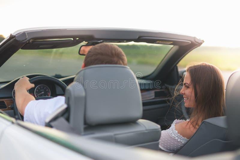 Το νέο ζεύγος έχει διακοπές που οδηγούν ένα άσπρο καμπριολέ στοκ φωτογραφία με δικαίωμα ελεύθερης χρήσης
