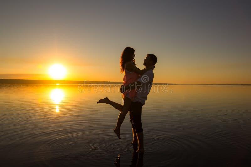 Το νέο ζεύγος αγκαλιάζει στο νερό στη θερινή παραλία Ηλιοβασίλεμα πέρα από τη θάλασσα Δύο σκιαγραφίες ενάντια στον ήλιο Ακριβώς π στοκ εικόνες με δικαίωμα ελεύθερης χρήσης