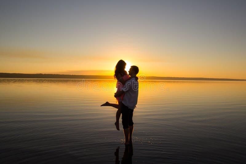 Το νέο ζεύγος αγκαλιάζει στο νερό στη θερινή παραλία Ηλιοβασίλεμα πέρα από τη θάλασσα Δύο σκιαγραφίες ενάντια στον ήλιο Ακριβώς π στοκ φωτογραφία με δικαίωμα ελεύθερης χρήσης