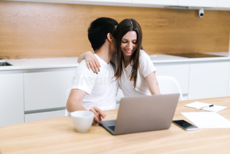 Το νέο ζεύγος αγκαλιάσματος χρησιμοποιεί τη συνεδρίαση φορητών προσωπικών υπολογιστών στην κουζίνα στο σπίτι στοκ φωτογραφία