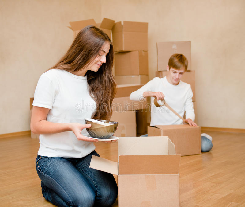 Το νέο ζεύγος βάζει τα πράγματα στα κουτιά από χαρτόνι για την κίνηση σε ένα καινούργιο σπίτι στοκ εικόνα