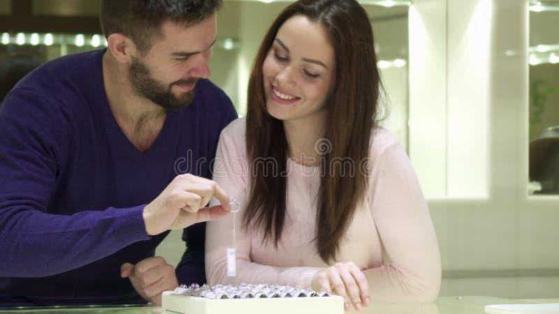 Το νέο ζεύγος επιλέγει τα δαχτυλίδια αρραβώνων στο κατάστημα κοσμήματος στοκ φωτογραφίες με δικαίωμα ελεύθερης χρήσης