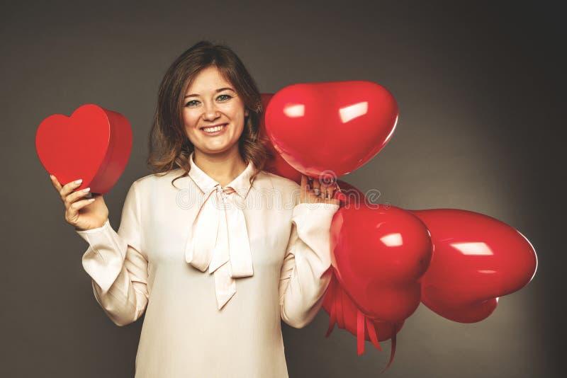 Το νέο ζεύγος με την καρδιά διαμόρφωσε τα κόκκινα μπαλόνια κοντά στον γκρίζο τοίχο στοκ εικόνα με δικαίωμα ελεύθερης χρήσης