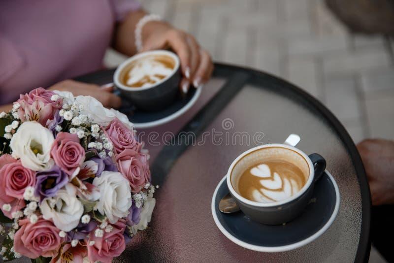 Το νέο ζεύγος πίνει το cofee Δύο φλυτζάνια του cofee που στέκονται στο cofee παρουσιάζουν παράλληλα με την κινηματογράφηση σε πρώ στοκ εικόνες με δικαίωμα ελεύθερης χρήσης
