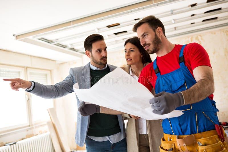 Το νέο ζεύγος παρουσιάζει στις handyman λεπτομέρειες οικοδόμων για τις ανακαινίσεις στοκ εικόνα με δικαίωμα ελεύθερης χρήσης