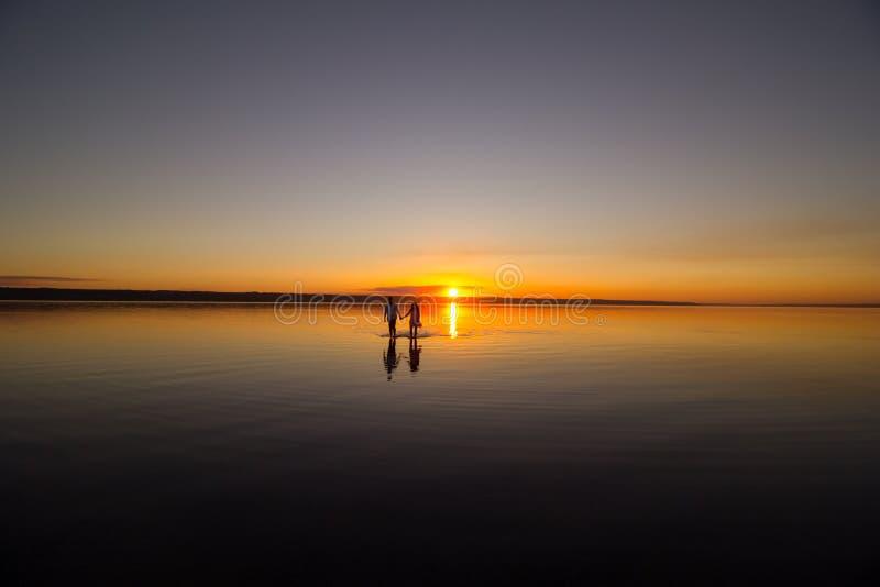 Το νέο ζεύγος περπατά μακριά στο νερό στη θερινή παραλία Ηλιοβασίλεμα πέρα από τη θάλασσα Δύο σκιαγραφίες ενάντια στον ήλιο Ακριβ στοκ φωτογραφίες