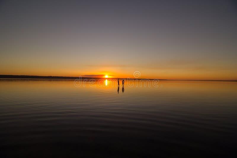 Το νέο ζεύγος περπατά μακριά στο νερό στη θερινή παραλία Ηλιοβασίλεμα πέρα από τη θάλασσα Δύο σκιαγραφίες ενάντια στον ήλιο Ακριβ στοκ φωτογραφία με δικαίωμα ελεύθερης χρήσης