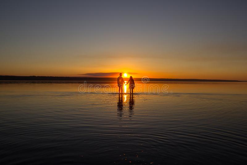 Το νέο ζεύγος περπατά μακριά στο νερό στη θερινή παραλία Ηλιοβασίλεμα πέρα από τη θάλασσα Δύο σκιαγραφίες ενάντια στον ήλιο Ακριβ στοκ εικόνα